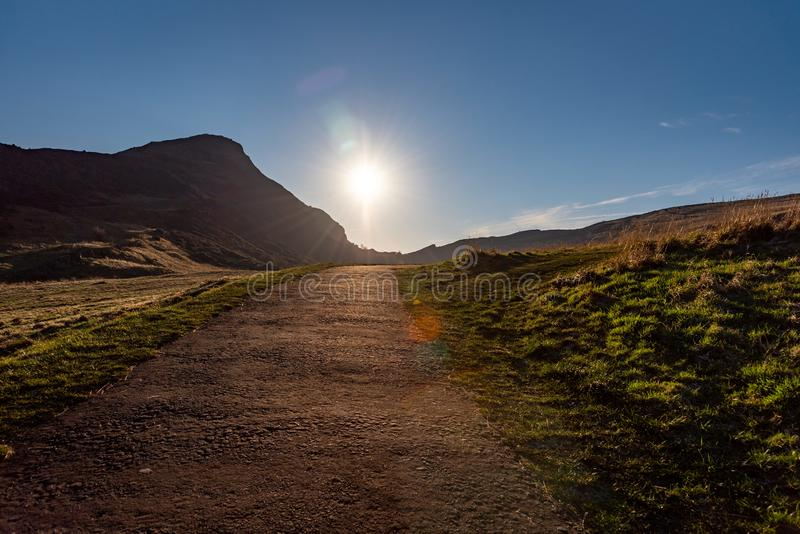 Path across the hills of Holyrood Park in Edinburgh, Scotland, with the sun rising bright at the end of the way. Popular. Destination for hiking and enjoying royalty free stock photos