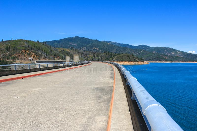 Path along the Shasta Dam offering great view of the reservoir, California, USA. Shasta Dam also known as Kennett Dam is a concrete arch-gravity dam royalty free stock image