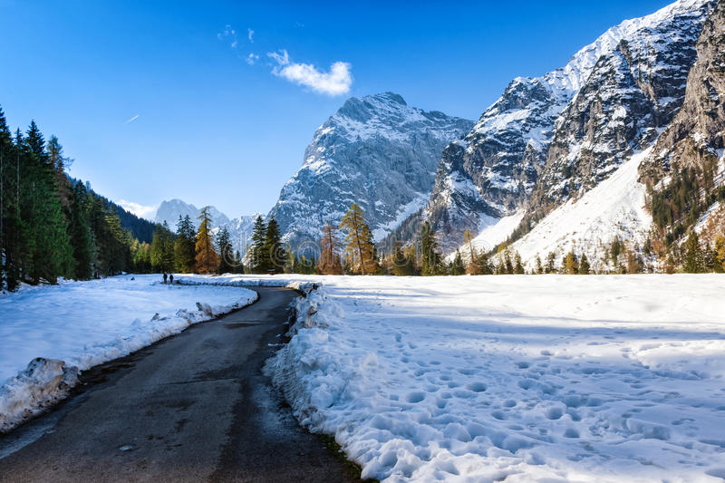 Path through early winter mountain landscape. Snow fall in the late autumn season stock images