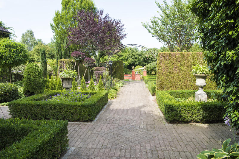Path in formal garden with boxwood beds stock photos