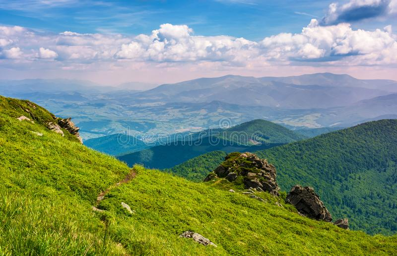 Grassy hillside over the cliff in mountains stock photo