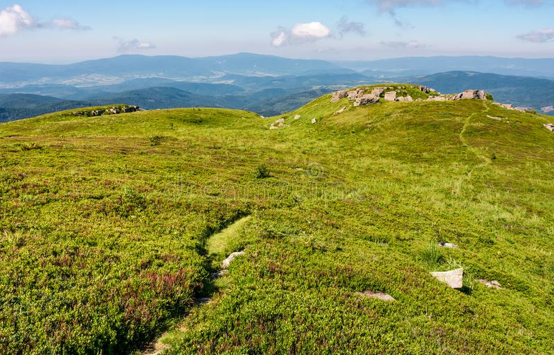 Path through grassy meadow to huge boulders royalty free stock photos