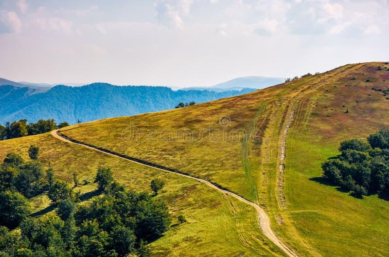Path through grassy meadows on mountain ridge royalty free stock images