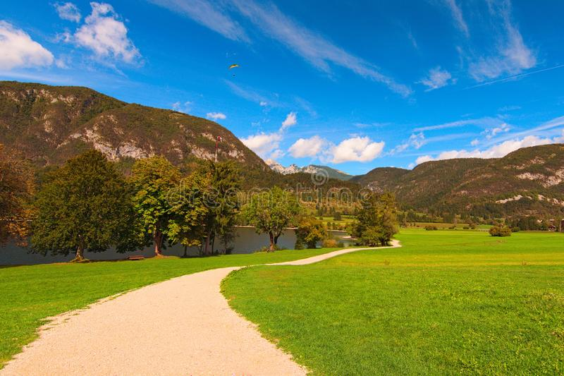 Path for hiking around picturesque Bohinj Lake in sunny autumn day. Beautiful nature landscape of lake and mountain range royalty free stock photography