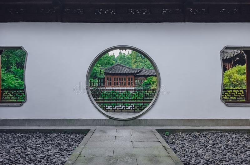 Path leading to moon gate with view of traditional Chinese building, in a Chinese garden, near West Lake, in Hangzhou, China stock photography