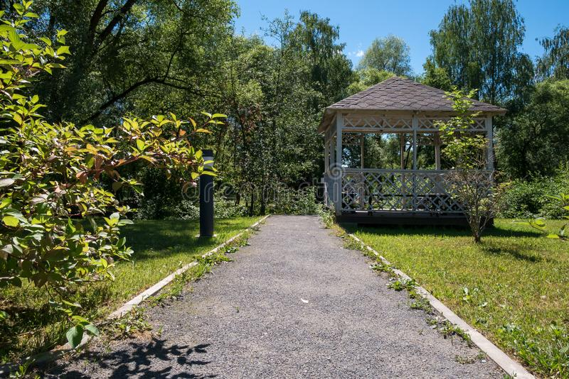 Path leading to wooden summerhouse standing among green trees royalty free stock image