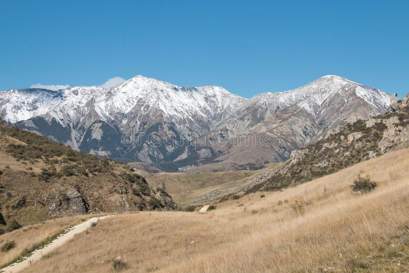Snow-capped mountains lie at the end of a path through rocky hillsides royalty free stock image