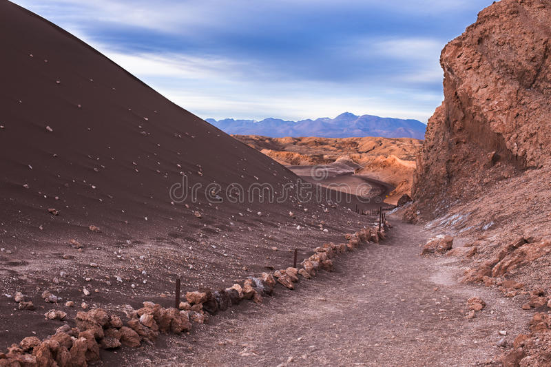 A path leads to a beautiful valley full of red and blue mountains while overcast by a stormy sky stock image