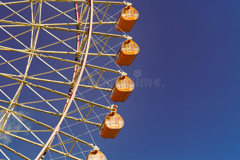 Path of orange funfair giant ferris wheel. With clear blue sky background royalty free stock images