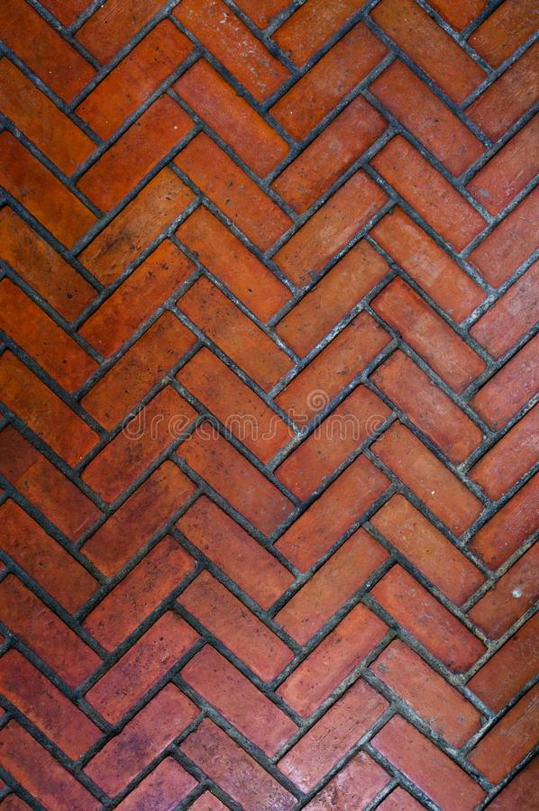 The path paved with red brick in herringbone pattern, Red stone walkway herringbone style pattern royalty free stock photography