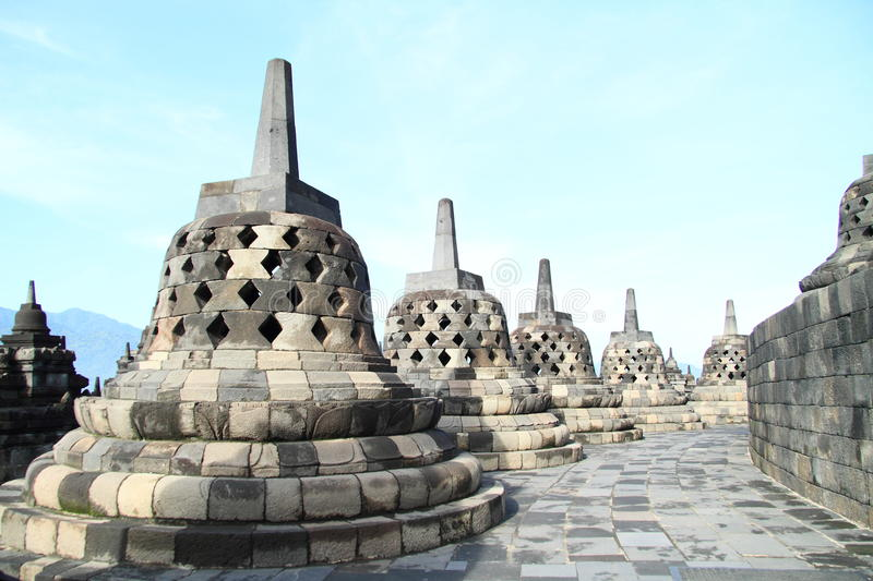 Path with stone bells on Borobudur. Path with wall and stone bells turning right on buddhist temple Borobudur (Java, Indonesia) with blue sky above stock photography