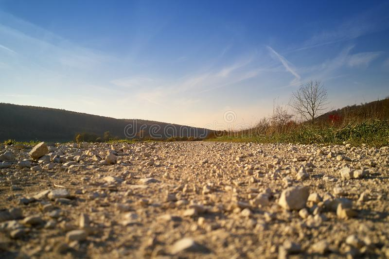 Path with stones from the bottom of the day. Path with stones from below in the day against a blue sky stock photo