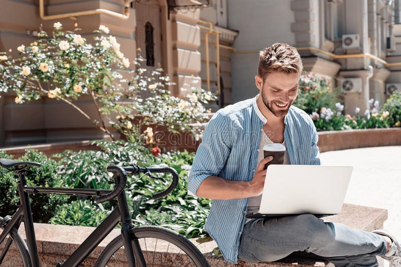 The path to success is to take massive action. Young smiling man sitting in the park, holding his laptop and a cup of stock photography