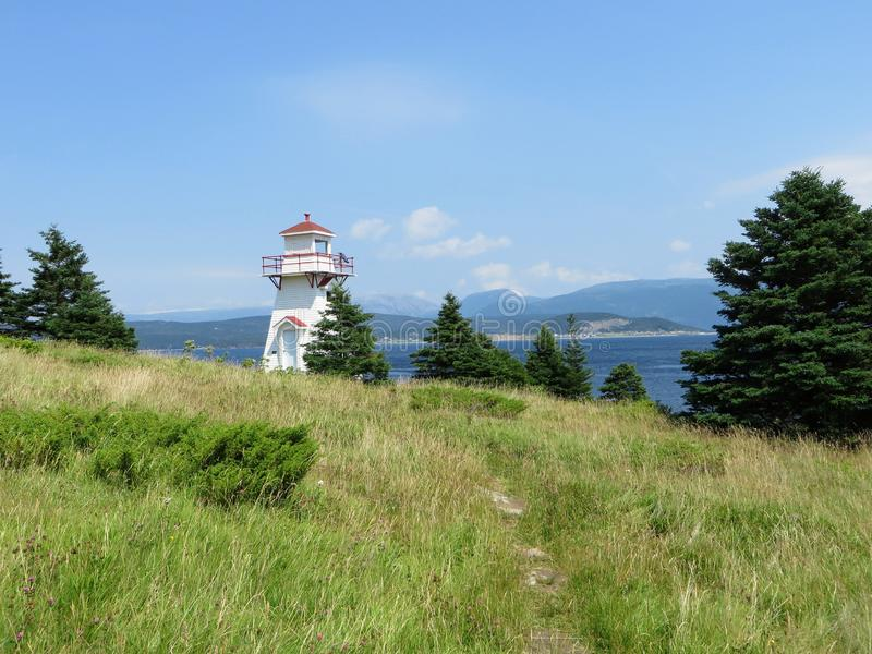 A path through to the tall grass to a small lighthouse at Woody Point, in Gros Morne National Park stock photography