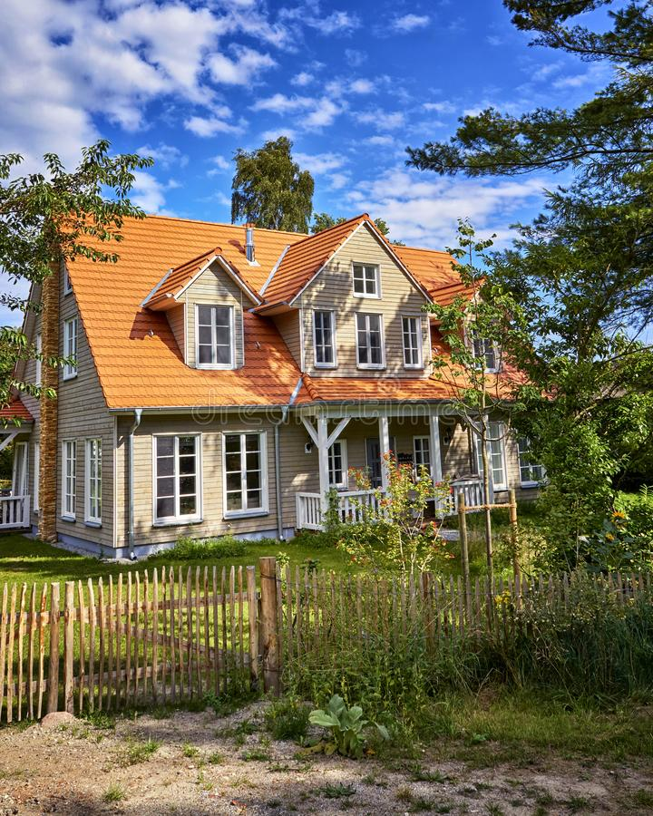 Path to the wooden house with wooden fence on the island Hiddensee. Home, holiday, timber, tree, cottage, summer, building, architecture, blue, europe, nature stock image