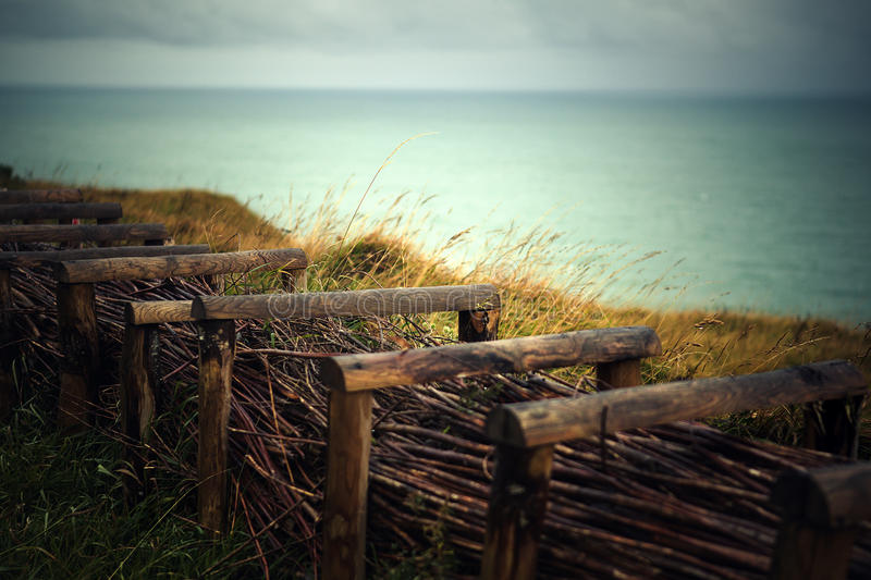 Path at the Top of the Cliffs at Fecamp Normany with wooden fence and barbed wire royalty free stock photo
