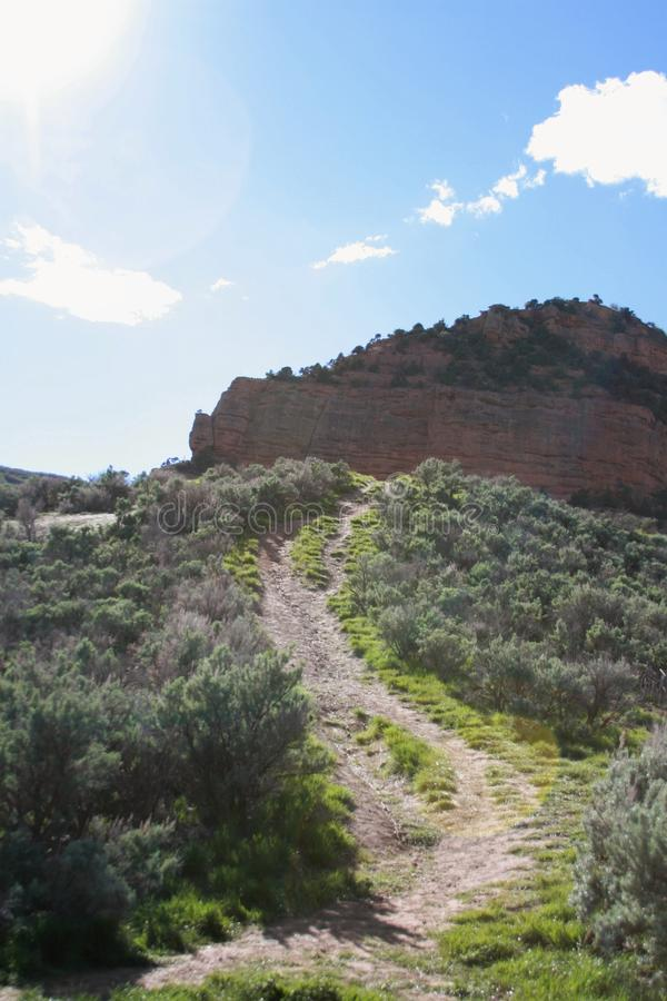 Path up the mountain through brush to a large rock formation stock photo
