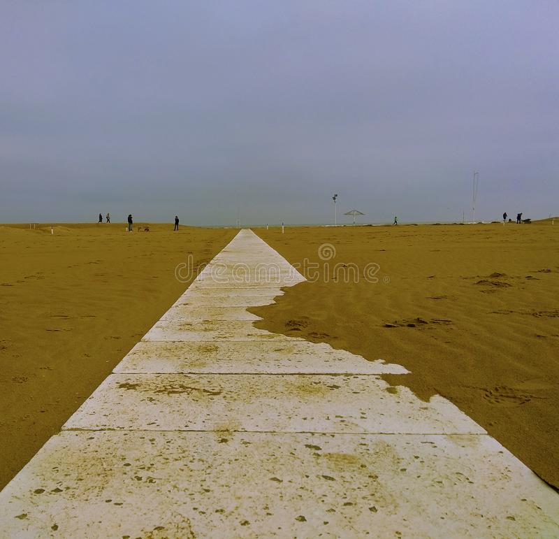 Path to the sea. Path, walkway of a bathhouse towards the Adriatic Sea in the middle of winter royalty free stock images