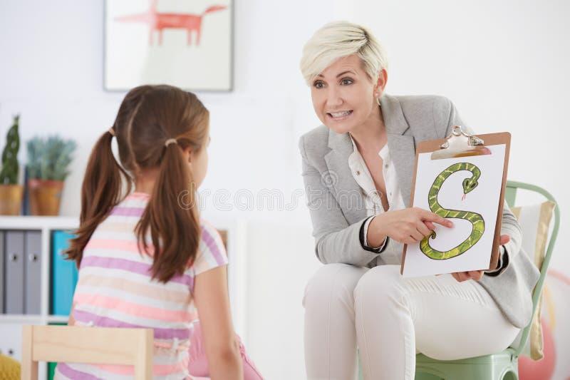 Pathologiste de la parole avec la jeune fille photos stock