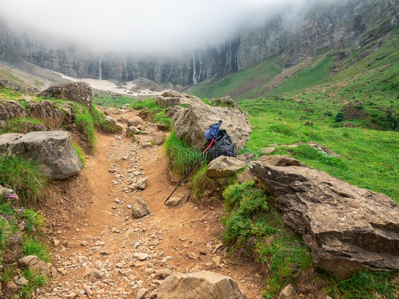 The path in the valley between the mountains with hiker equipment. The pathpath leading to a waterfall in the valley between the mountains with hiker equipment stock photography