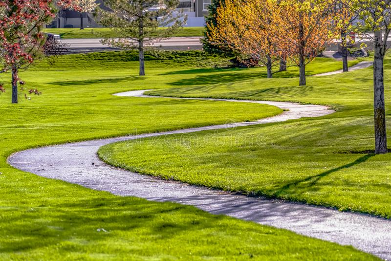 Pathway curving amid a lush field with young colorful trees on a sunny day. The winding walkway leads to the paved road in the distance royalty free stock photography
