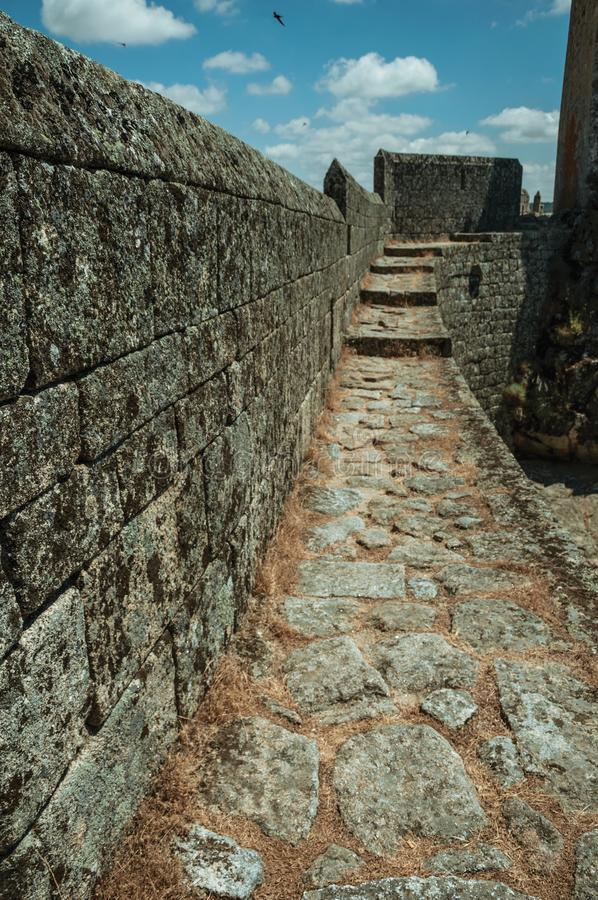 Pathway over thick stone wall in a castle. Pathway with dry grass on thick stone wall, in a sunny day at the Sortelha Castle. One of the most astonishing and stock images