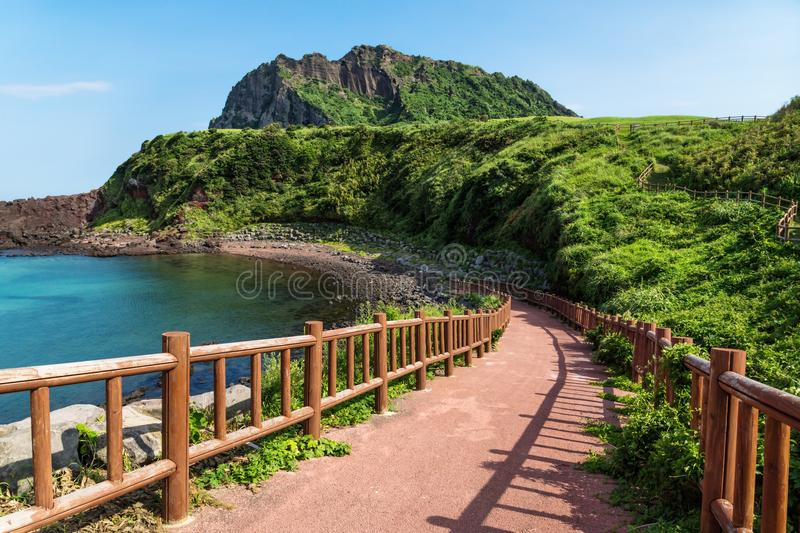 Pathway leading to beach with view over ocean and Ilchulbong, Seongsan, Jeju Island, South Korea. Pathway leading to beach with view over ocean and and volcano stock images