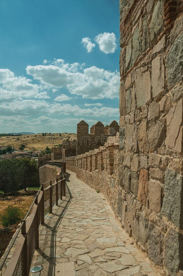 Pathway over old thick wall encircling the town of Avila. Pathway over old thick wall with battlement and large tower made of stone encircling the town of Avila stock image