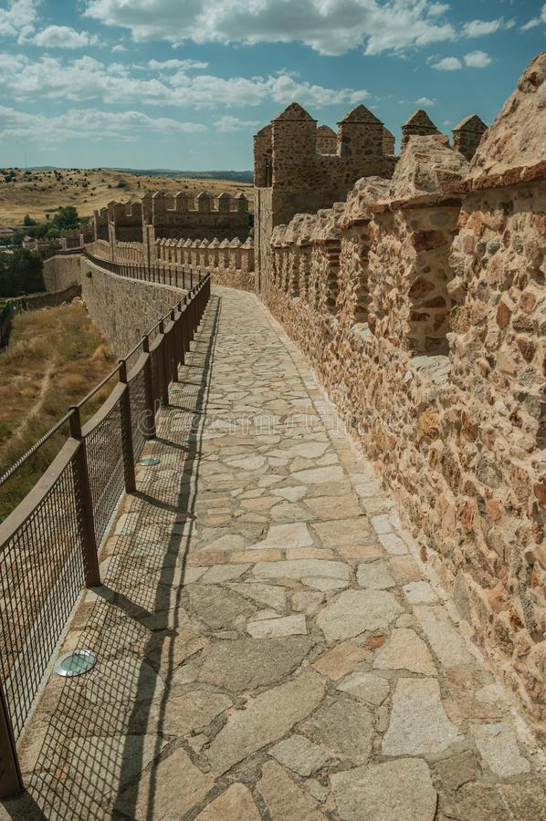 Pathway over old thick wall encircling the town of Avila. Pathway over old thick wall with battlement and large tower made of stone encircling the town of Avila royalty free stock image