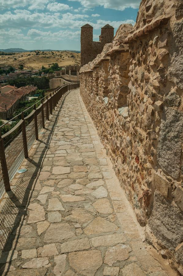 Pathway over old thick wall encircling the town of Avila. Pathway over old thick wall with battlement and large tower made of stone encircling the town of Avila stock photos