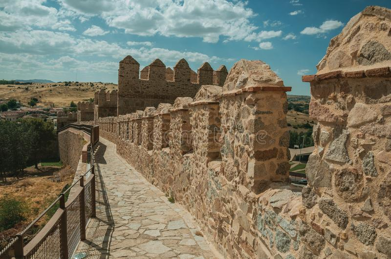 Pathway over old thick wall encircling the town of Avila. Pathway over old thick wall with battlement and large tower made of stone encircling the town of Avila royalty free stock photo