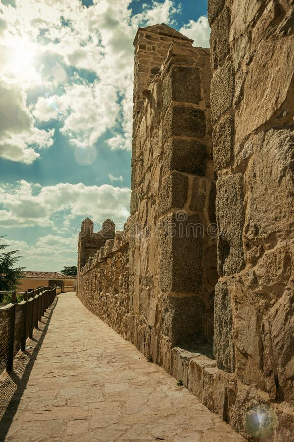 Pathway over old thick wall encircling the town of Avila. Pathway over old thick wall with battlement made of stone encircling the town of Avila. It has the stock image