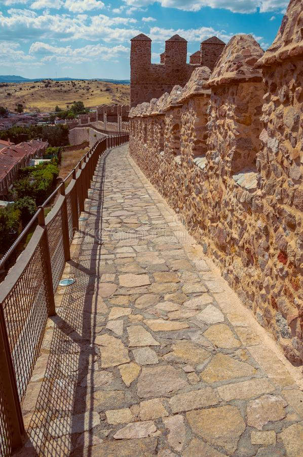 Pathway over old thick wall encircling the town of Avila. Pathway over old thick wall with battlement made of stone encircling the town of Avila. It has the stock photo
