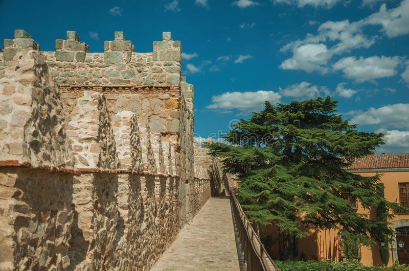 Pathway over old thick wall with large tower in Avila. Pathway over old thick wall with battlement and large tower made of stone encircling the town of Avila. It royalty free stock images