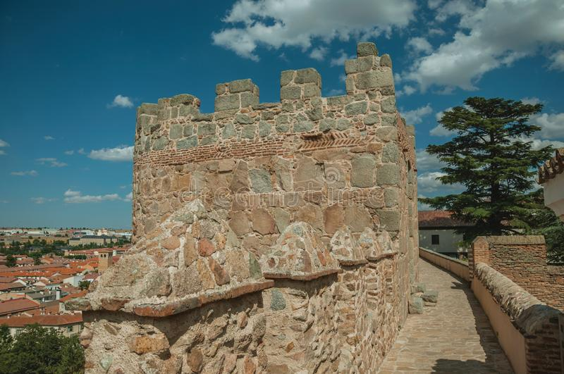 Pathway over old thick wall with large tower in Avila. Pathway over old thick wall with battlement and large tower made of stone encircling the town of Avila. It stock photos