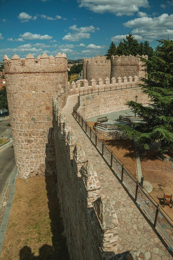 Pathway over old thick wall with large towers in Avila. Pathway over old thick wall with battlement and large towers made of stone encircling the town of Avila stock image