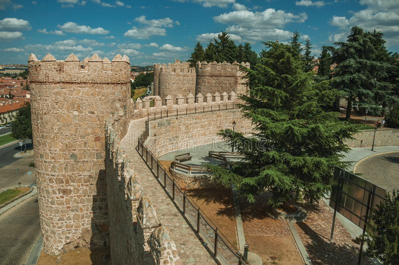 Pathway over old thick wall with large towers in Avila. Pathway over old thick wall with battlement and large towers made of stone encircling the town of Avila stock photos