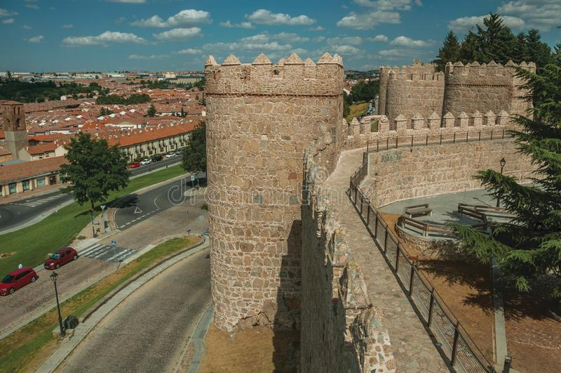 Pathway over old thick wall with large towers in Avila. Pathway over old thick wall with battlement and large towers made of stone encircling the town of Avila royalty free stock image