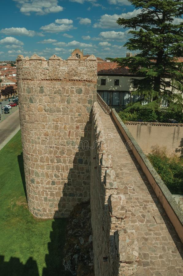 Pathway over old thick wall with large towers in Avila. Pathway over old thick wall with battlement and large tower made of stone encircling the town of Avila royalty free stock images