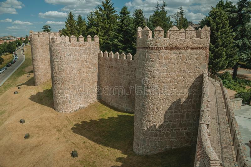 Pathway over old thick wall with large towers in Avila. Pathway over old thick wall with battlement and large tower made of stone encircling the town of Avila stock image