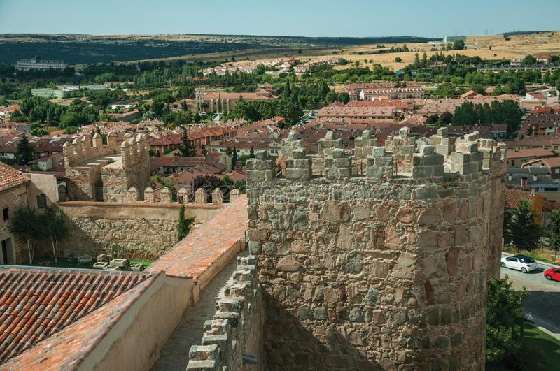 Pathway over old thick wall with large towers at Avila. Pathway over old thick wall with battlement and large tower made of stone encircling the town of Avila royalty free stock photography