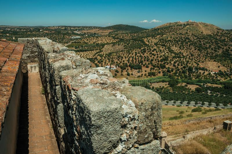 Pathway over stone wall and a fortress on top of hill. Pathway on top of thick stone wall in a sunny day, with the Fort of Nossa Senhora da Graça on top of royalty free stock photography