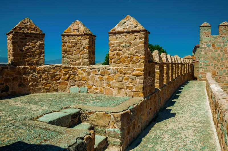 Pathway over thick stone wall with battlement around Avila. Pathway over thick stone wall with battlement and merlons around the town at Avila. It has the royalty free stock image