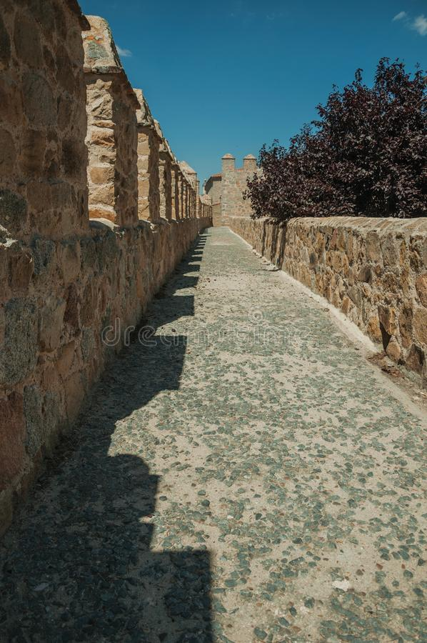 Pathway over thick stone wall with battlement around Avila. Pathway over thick stone wall with battlement and merlons around the town, in a sunny day at Avila stock photos