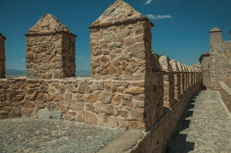 Pathway over thick stone wall with battlement around Avila. Pathway over thick stone wall with battlement and merlons around the town, in a sunny day at Avila stock photo