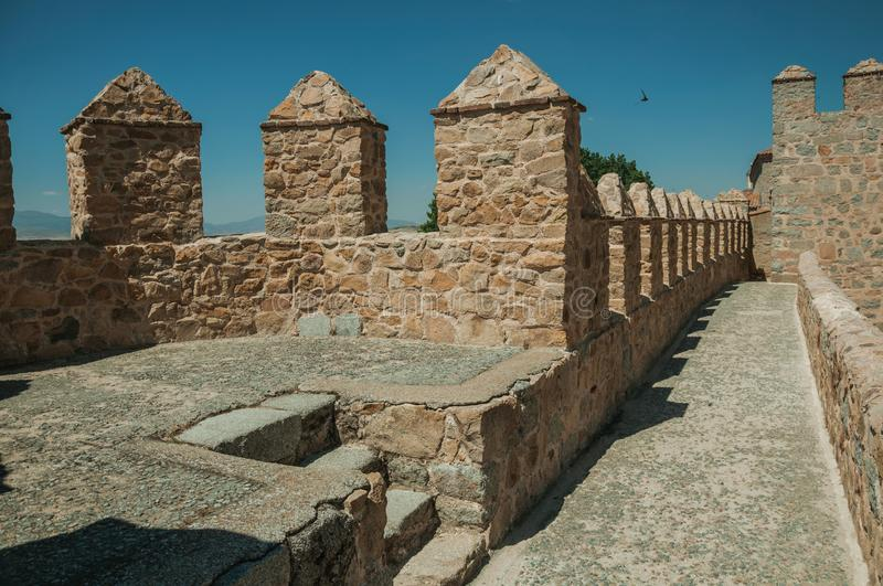 Pathway over thick stone wall with battlement around Avila. Pathway over thick stone wall with battlement and merlons around the town, in a sunny day at Avila stock images