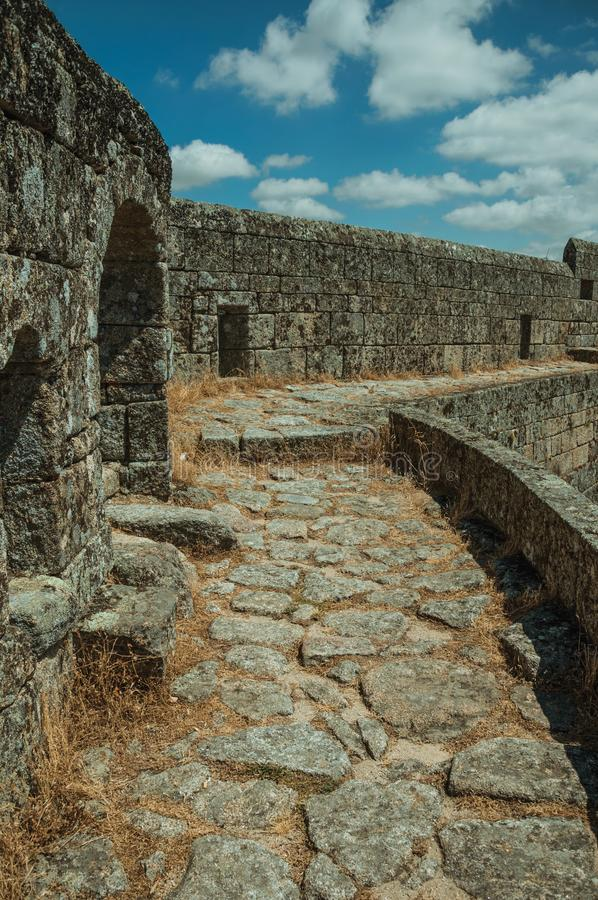 Pathway over thick stone wall in a castle. Close-up of pathway with dry grass on thick stone wall, in a sunny day at the Sortelha Castle. One of the most royalty free stock photography