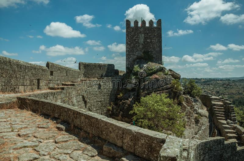 Pathway over wall and tower from keep in a castle. Pathway over thick stone wall with square tower from keep, in front of green rocky courtyard at the Sortelha royalty free stock images