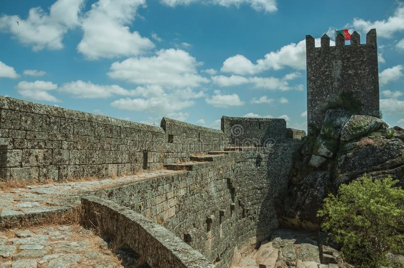 Pathway over wall and tower from keep in a castle. Pathway over thick stone wall with square tower from keep, in front of green rocky courtyard at the Sortelha stock images