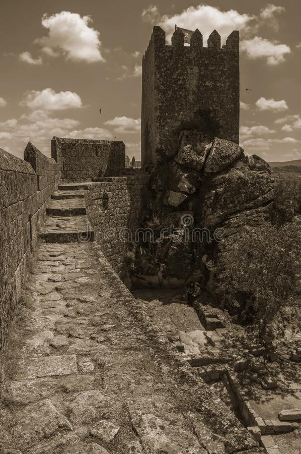 Pathway over wall and tower from keep in a castle. Pathway over thick stone wall with square tower from keep at the Sortelha Castle. One of the most astonishing stock photo